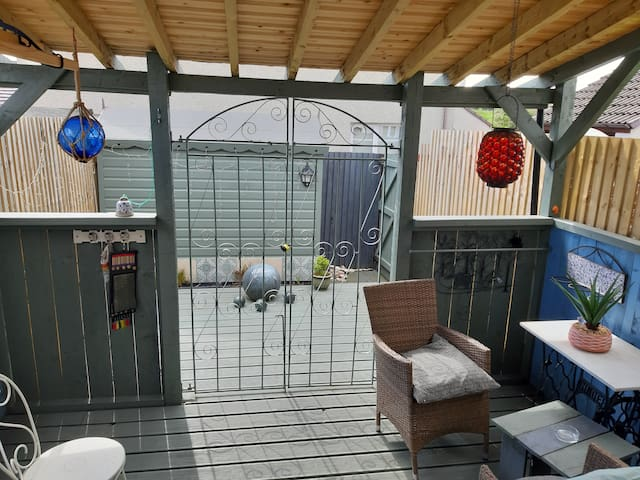House & adjoining  rustic outdoor room & parking