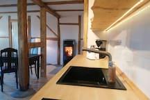 Küche mit Kühlschrank, 2-Platten-Herd, Toaster, Kaffeemaschine und Wasserkocher.