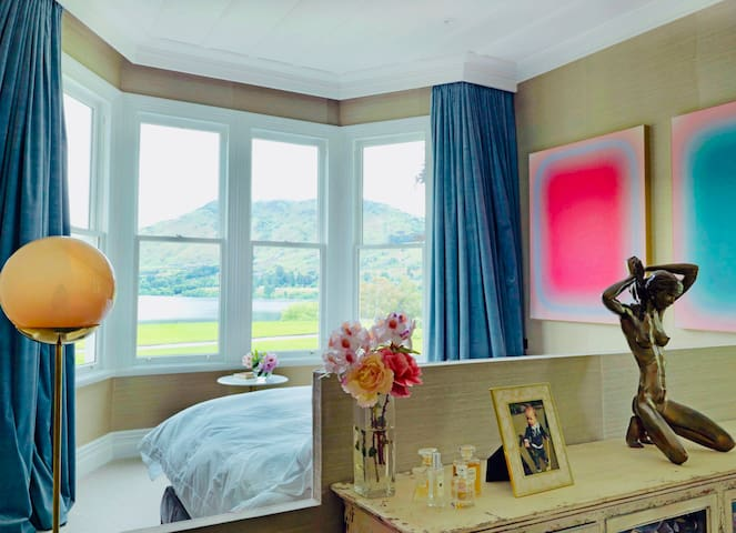 The Californian king bed sits in the middle of this large room facing the views out of the bay window