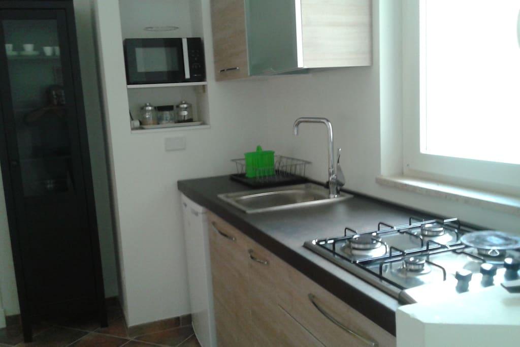 Cucina attrezzata con frigorifero, forno a microonde, etc