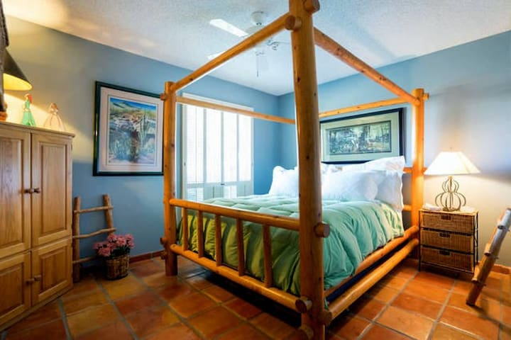 Queen-size bed in one of four guest bedrooms.  There is a television in that TV armoire.
