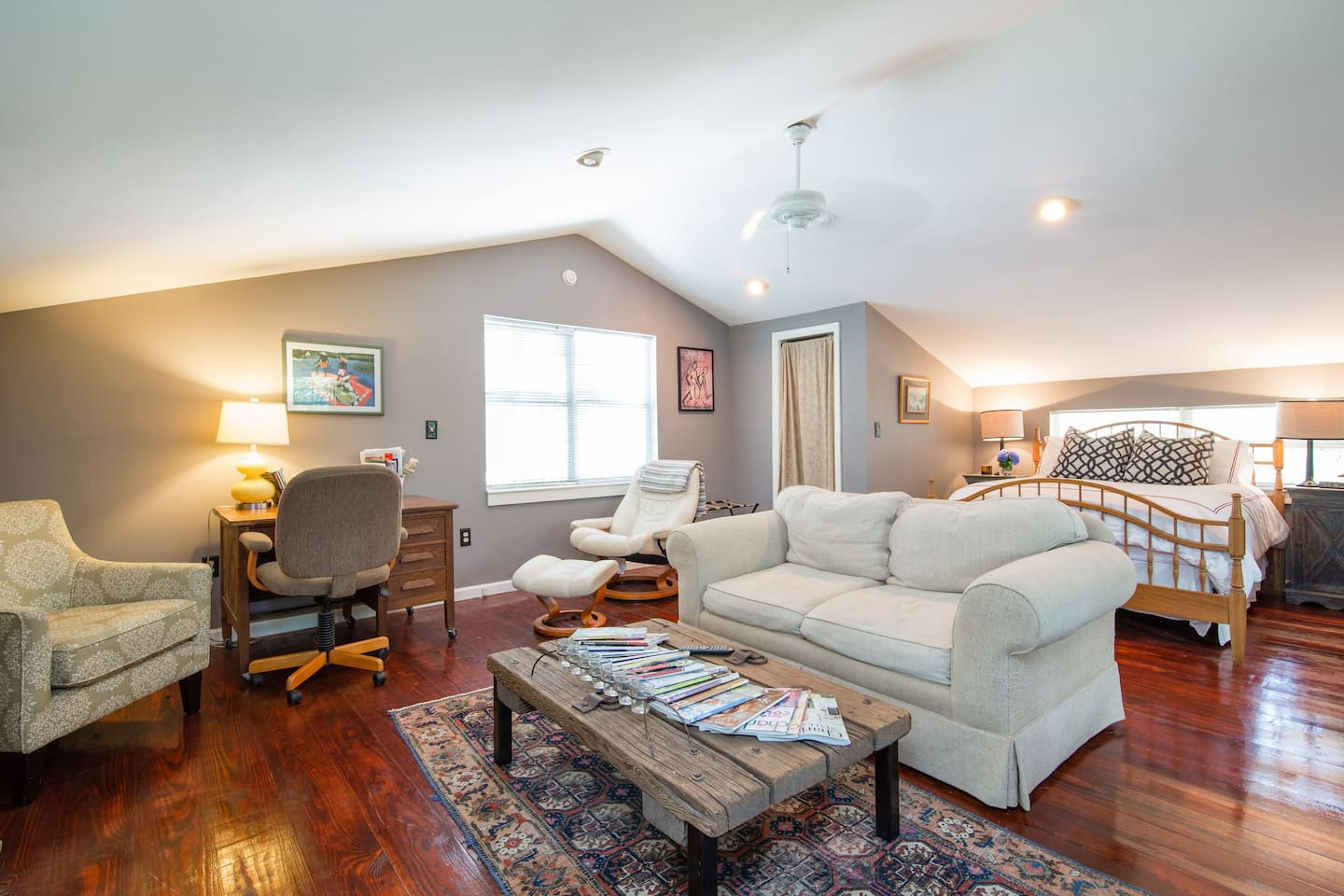 A large space with a full sized bed, love seat, lounge chairs, and a desk