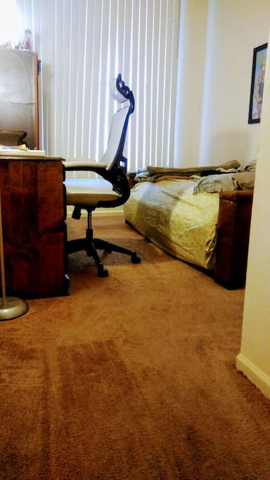 Updated photo: guest room includes futon with fresh blankets, towels, office chair and desk for work/business.