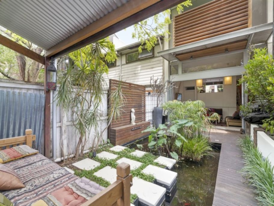 The back garden features a fish pond and daybed where you can relax.