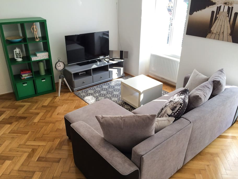 Spacious living room with large couch&sofa, flat TV and dining table