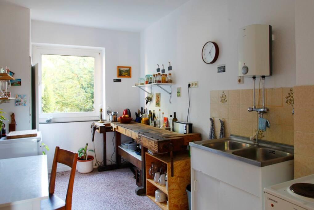 Küche mit historischer Werkbank, Kühlschrank, Herd, Kochfeld, Terrazzoboden, Tisch für 2 Personen (optional kann ein 3. Stuhl gestellt werden)