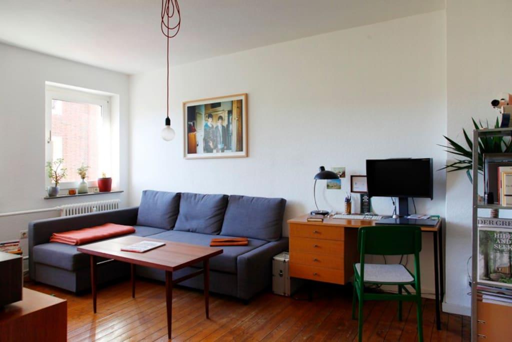 Wohnzimmer mit Echtholz Dielen, gemütlicher Schlafcouch, WLAN, Schreibtisch