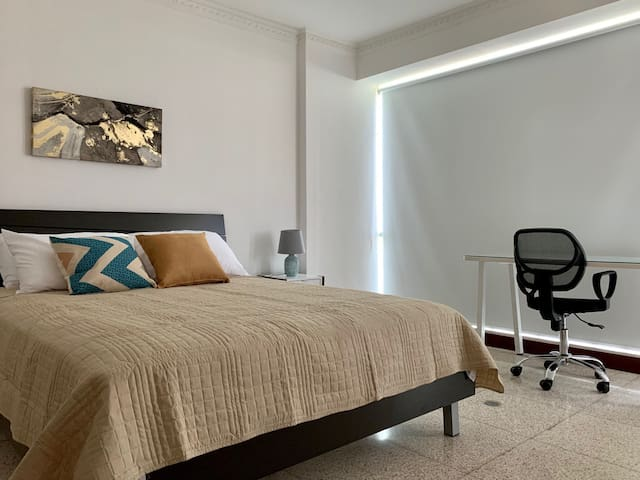 Master bedroom with a queen bed and a desk