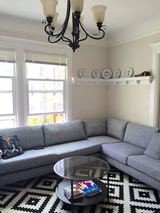 Living room with dining table, large sectional couch, and large TV.