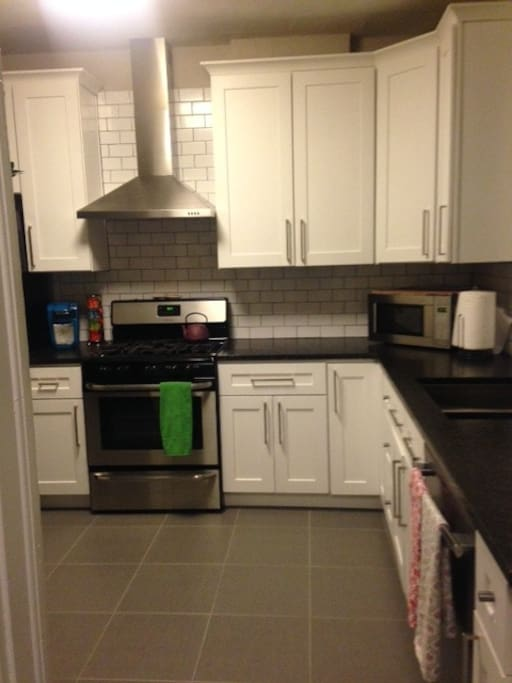 Updated and stocked kitchen with modern appliances, including gas stove/oven, toaster oven, microwave, dishwasher, fridge with filtered water, and a coffee pot.