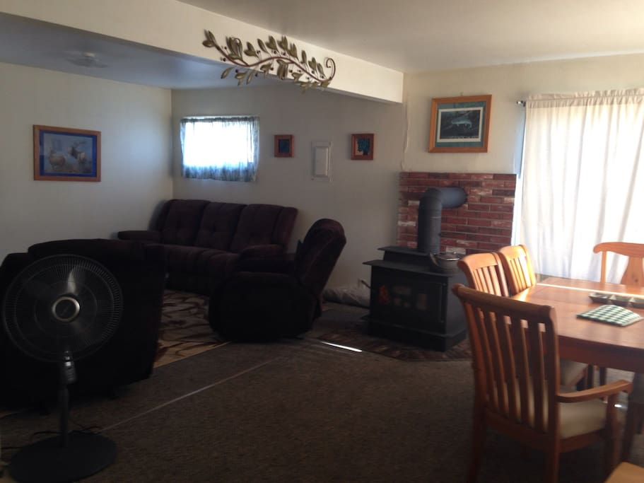 Spacious living room features DVD player/TV, reclining sofa and two comfy lazy boy chairs.