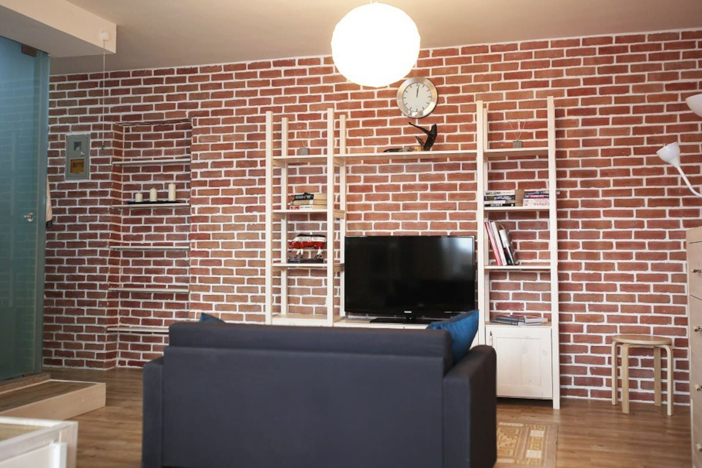 A nice little living room with a cozy couch, the TV and some storage unites.