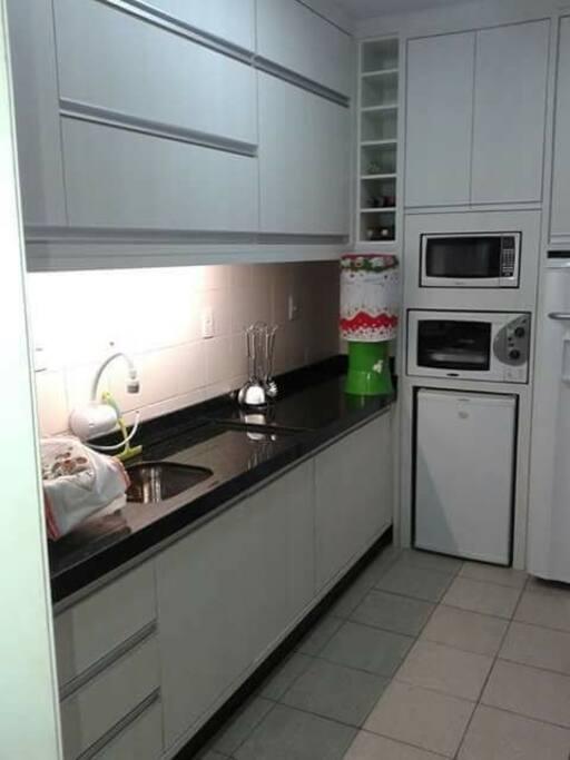 cozinha com forno elétrico, microondas, freezer, geladeira.