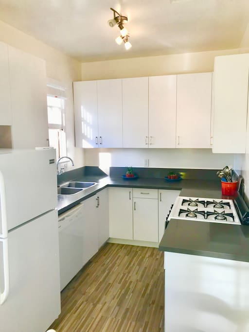 Beautiful and bright kitchen accompanied by a gas range and quartz countertops for all of your cooking needs