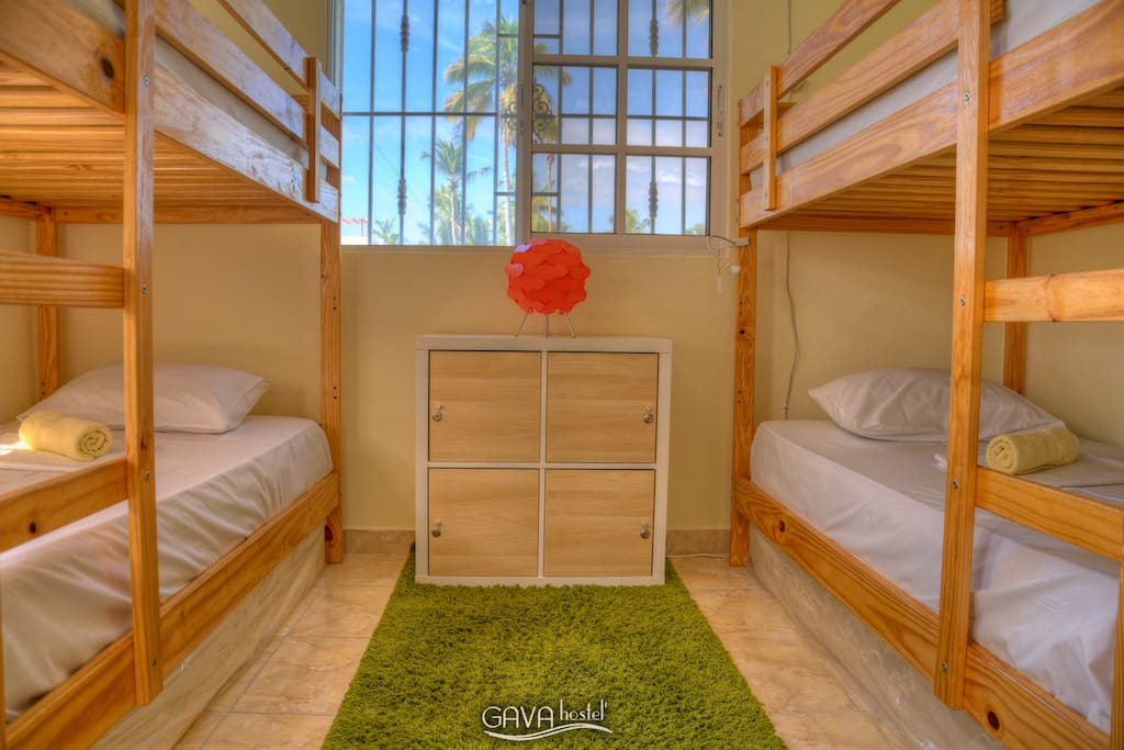 Four-bed dormitory with shared bathroom and a personal locker.