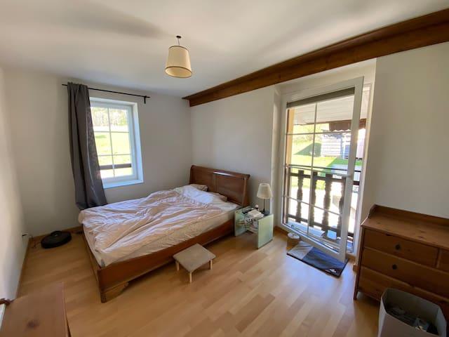 Belle chambre équipée d'un lit double, meuble tiroir, penderie ouverte, table pouvant faire office de bureau et table de chevet