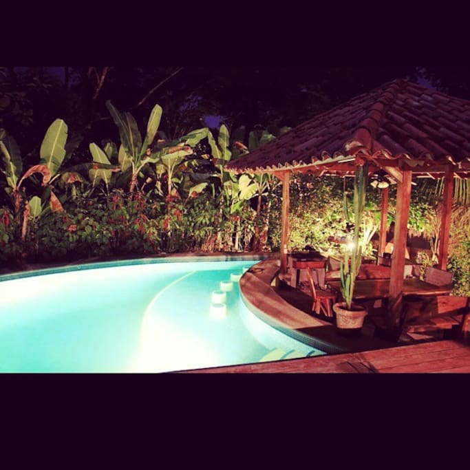 Pool and outdoor kitchen area at night.