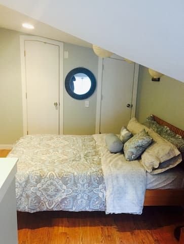 The upper loft master suite overlooks the kitchen  and has its own 1/2 bath.