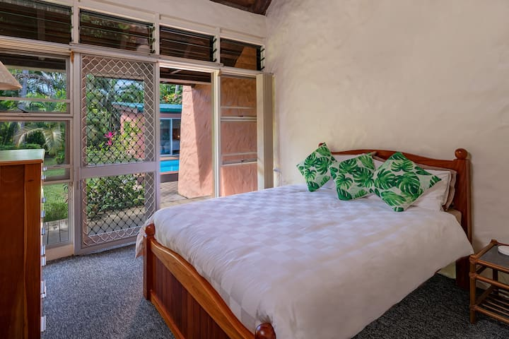 Renewed second bedroom sleeps two with queen bed and private bathroom with direct outdoor and pool access