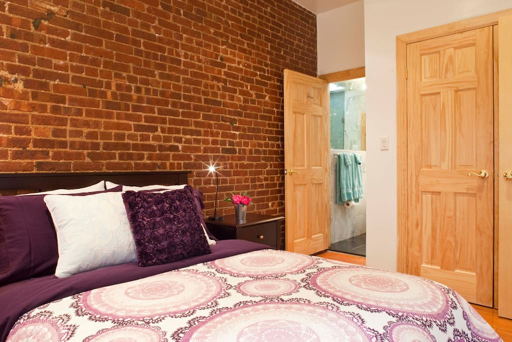 Big beautiful bedroom with original exposed brick accent wall