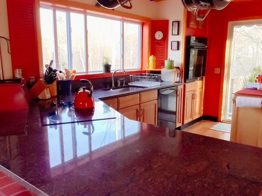 Fully stocked, open-concept kitchen with granite island opens onto side deck facing Acadia.