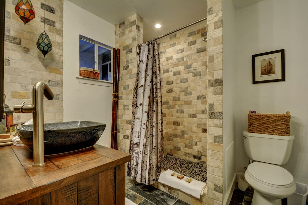 The walk-in shower with a bench has stone tiled walls and a natural pebble tile floor that is truly luxurious