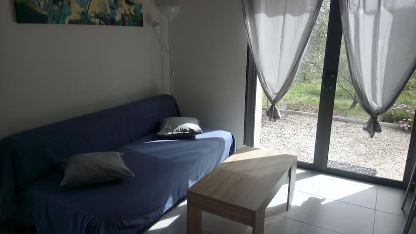 Salon avec canapé-lit donnant sur le jardin