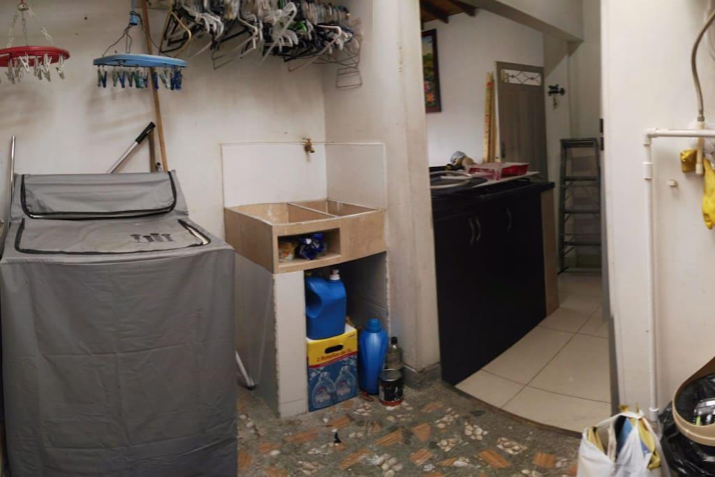 zona de ropas con lavadora, mesa para planchar, lavadero y soporte para extendido