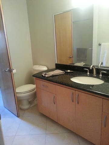 Private bathroom; view from entry through the bedroom. Marble floor, granite counter, huge mirror.