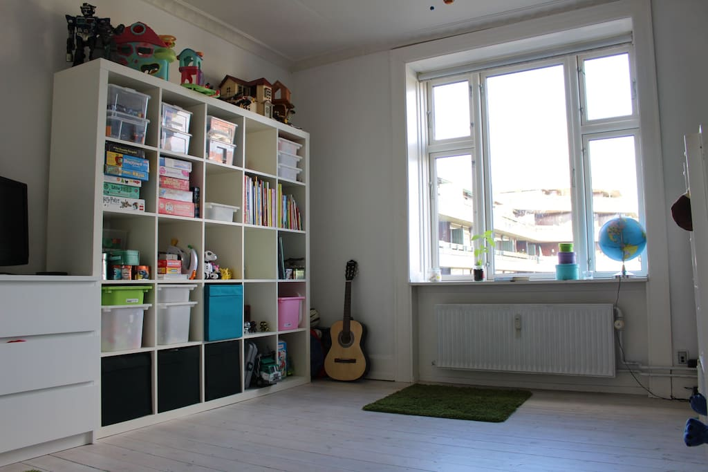 Children's room with toys and twin sized bunk beds.