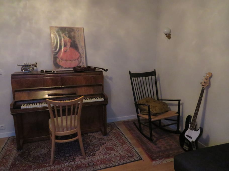 Cozy living room with soft sofa, rocking, chandelier and lots of instruments.