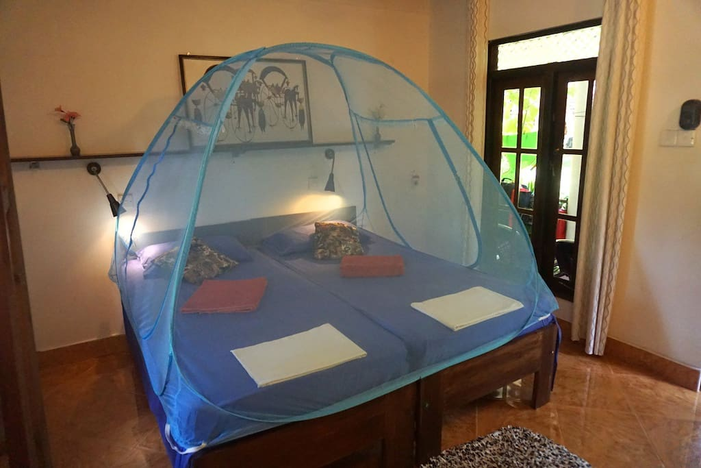 Beds, pushed together and with optional mosquito net. The beds are very comfortable with thick, dual-padded spring mattresses.