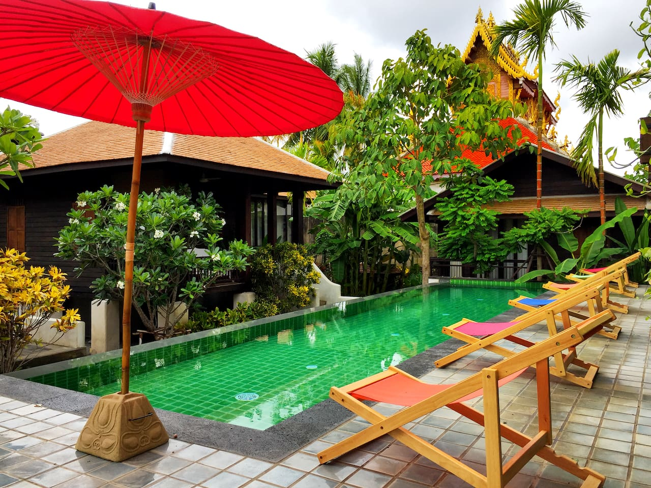Outdoor pool with elevated poolbar and view of Wat Saen Fang