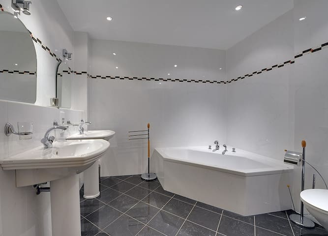 Luxe badkamer met ligbad dubbele wastafel en stoomcabine