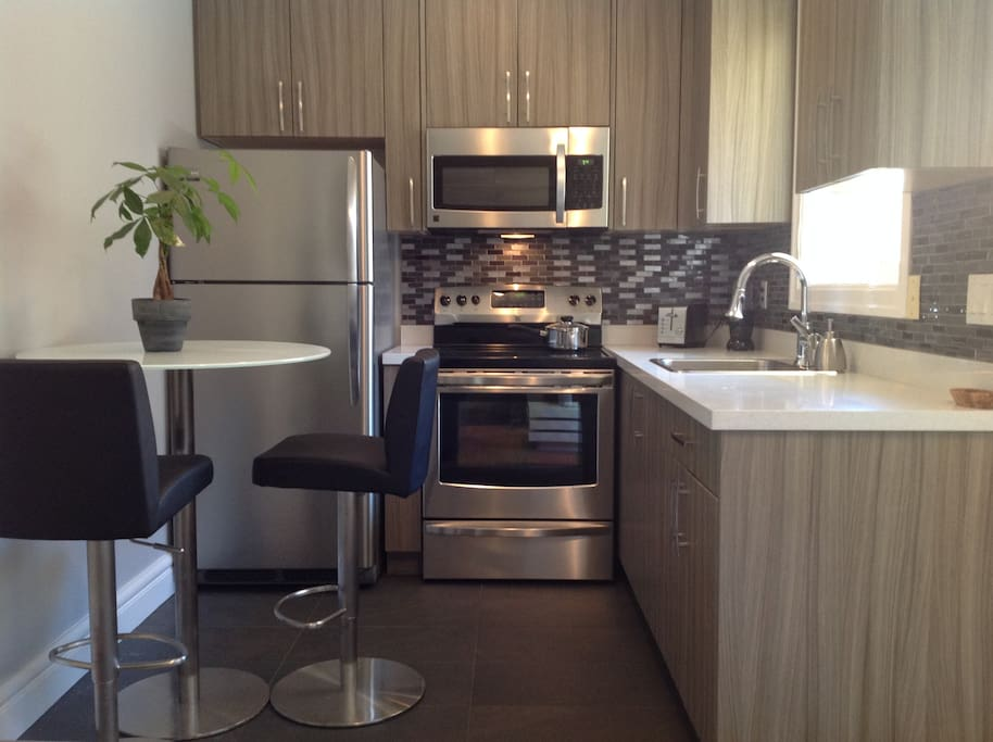 kitchen with new, stainless steel appliances and modern dishes.