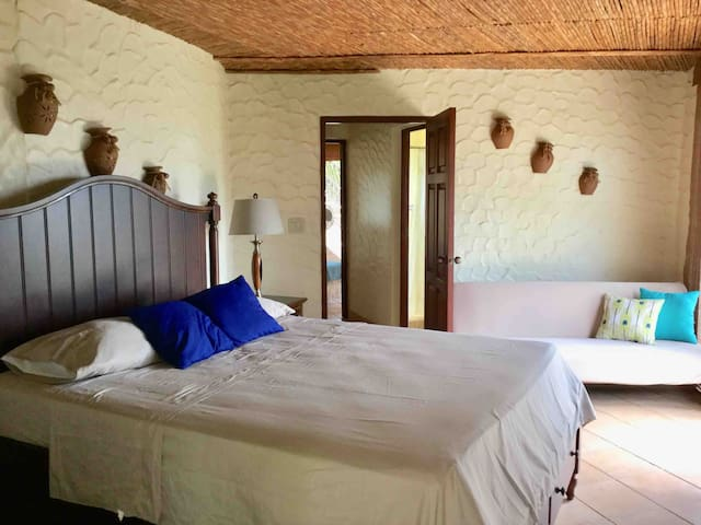 Guest house bedroom with fans and sofa