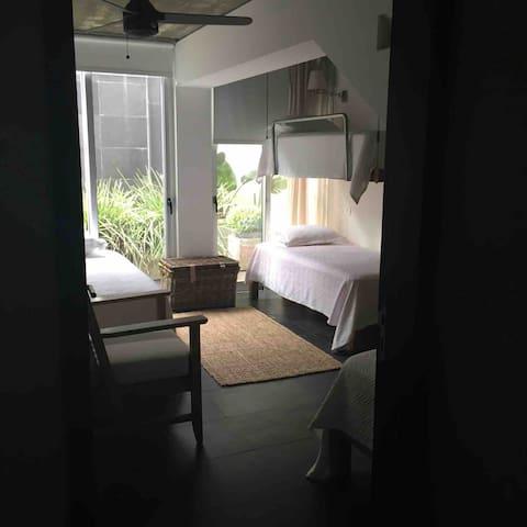 dormitorio con cuatro camas singles que comparten el baño con el dormitorio para matrimonio
