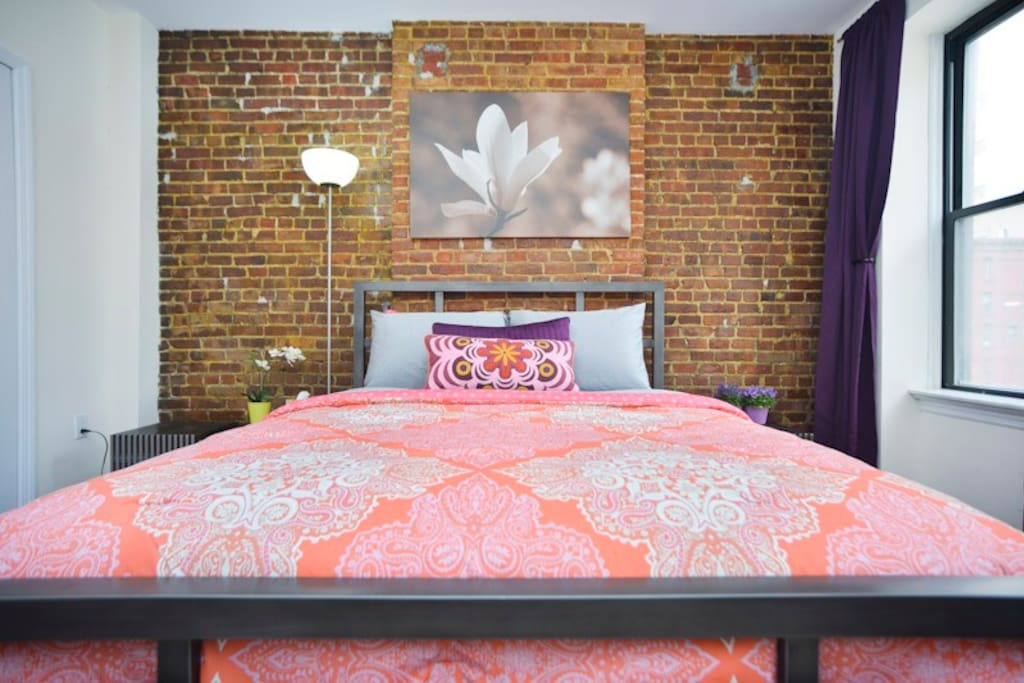 Queen size bed with metal frame. Brick accent wall.