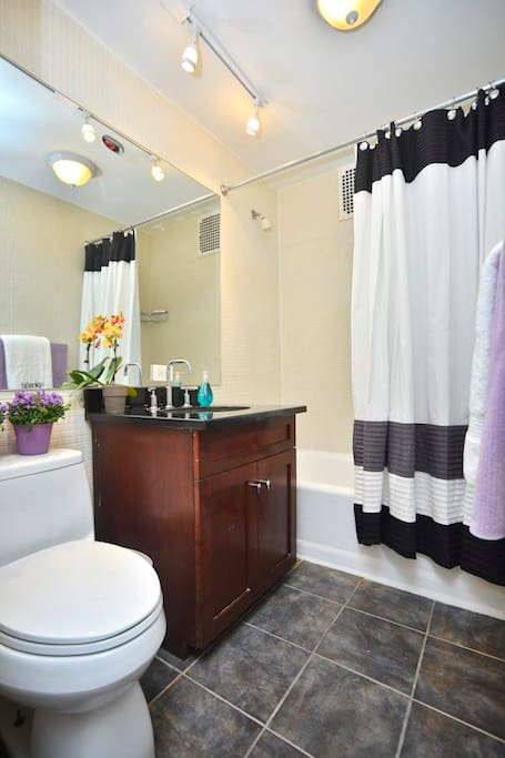 Bathroom with stylish porcelain tiles on the floor and granite vanity top