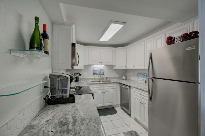 Gorgeous updated stainless kitchen stocked with dishes, and necessary appliances.