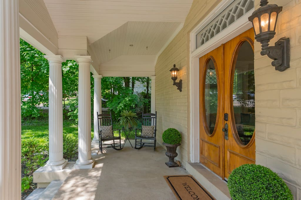 Stately wrap around front porch with rocking chairs and seating for the entire group.