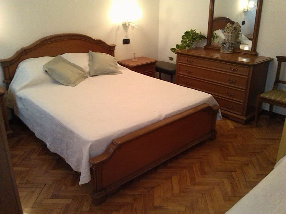 Camera con letto matrimoniale pavimento legno.Big  bedroom with 1 double bed and parquet floor.