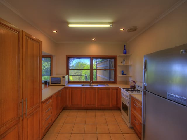 Kitchen with large refrigerator, gas stove/oven and large microwave.