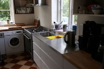 Køkken med opvaskemaskine, vaskemaskine, stort gaskomfur og kaffemaskine