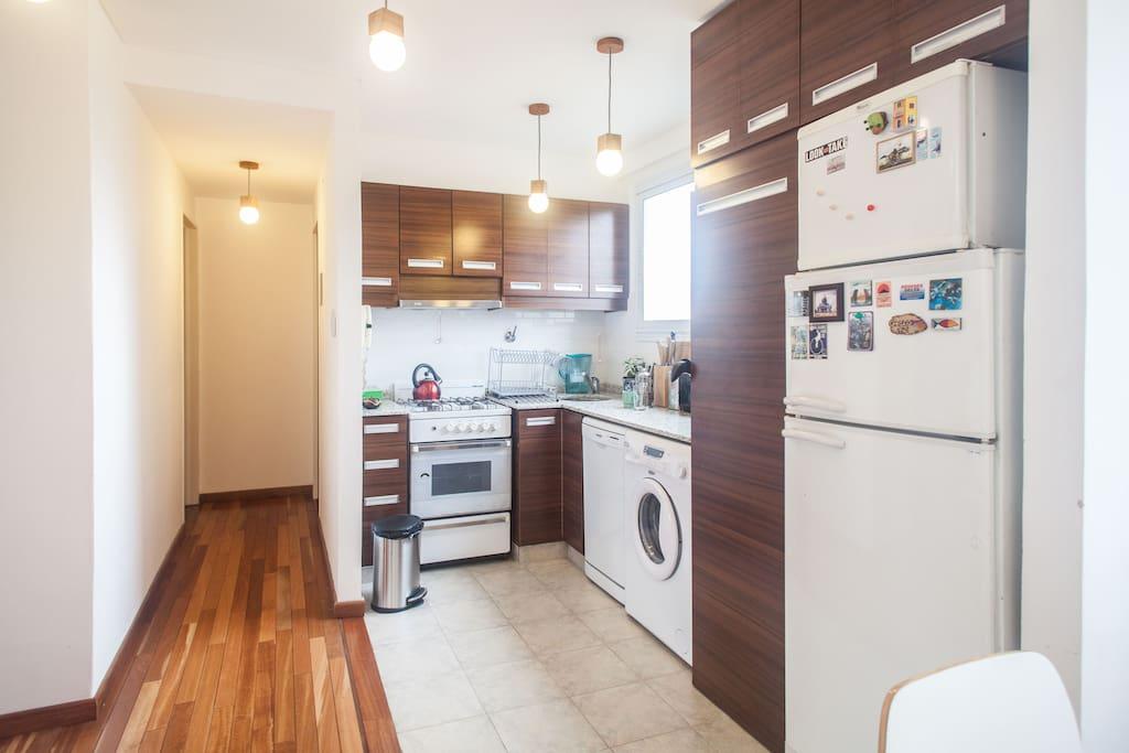 Fully equipped kitchen and corridor leading to the  bathroom. /Cocina completa con el corredor que da al baño (fondo a la derecha)