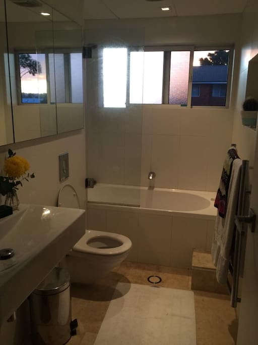 Newly renovated bathroom with travertine tiles, heated towel rack, bath and shower.