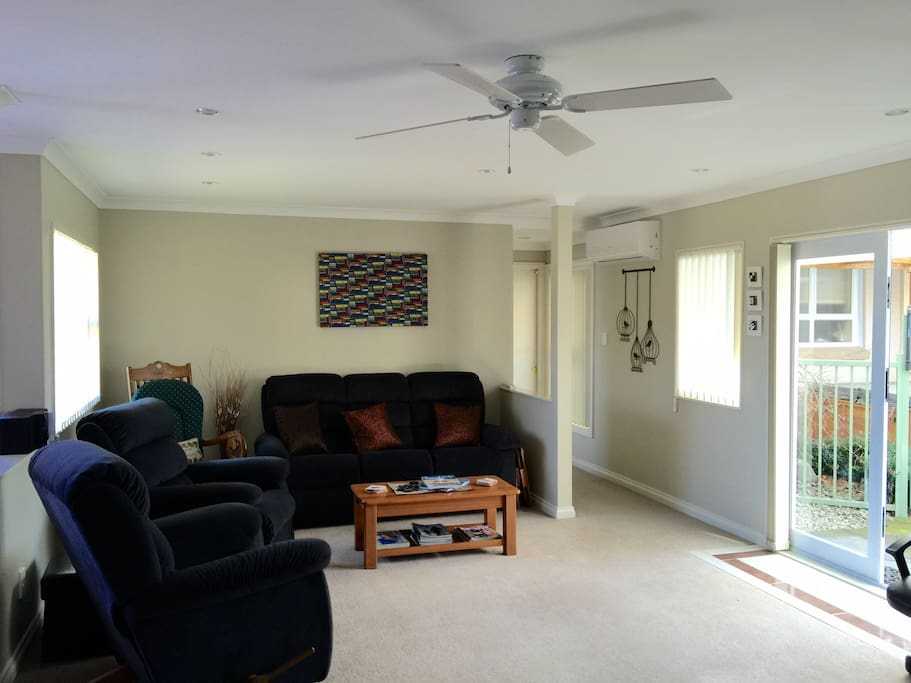 Lounge with Ceiling Fan and Heat Pump with French doors leading to garden court yard area.
