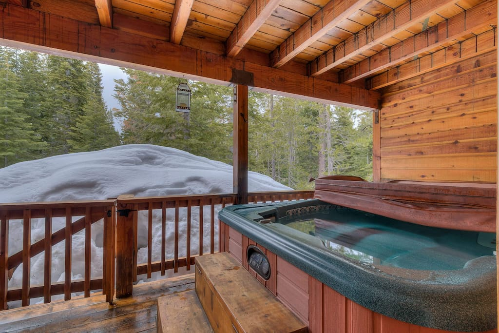 The lower-level patio features a sheltered hot tub that is perfect for all seasons.