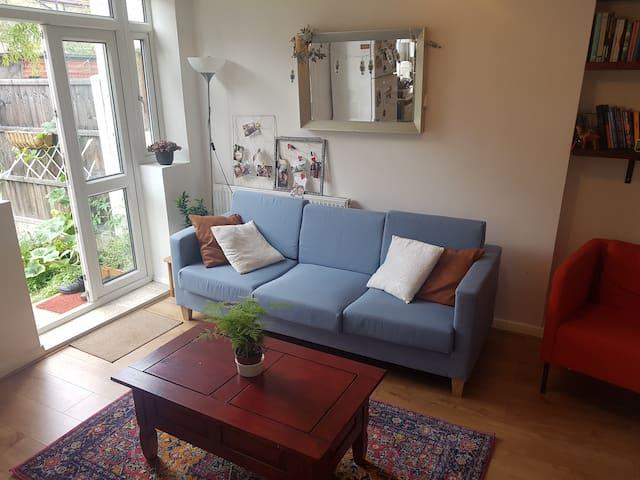 Living room - large sofa, armchair, book shelf and desk.