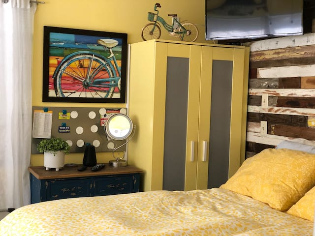 Queen bed, smart TV with cable, light up mirror, and small wardrobe.
